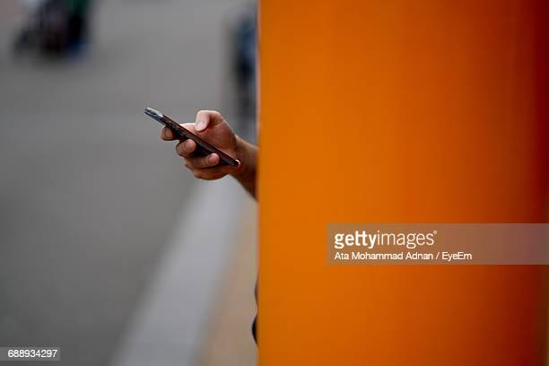 Cropped Hand Holding Mobile Phone By Orange Wall