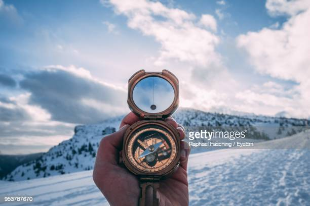 cropped hand holding navigational compass against sky - guidance stock pictures, royalty-free photos & images