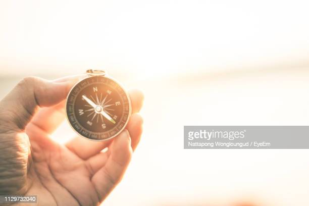 cropped hand holding navigational compass - 方位磁針 ストックフォトと画像