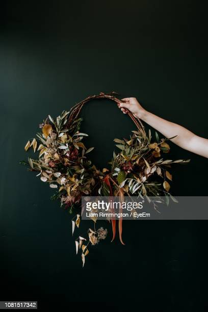 cropped hand holding of woman wreath on wall - wreath stock pictures, royalty-free photos & images