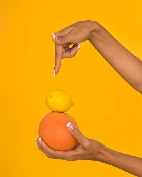 Cropped hand holding orange against orange background