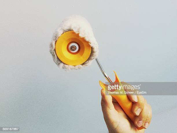 Cropped Hand Holding Paint Roller Against White Background