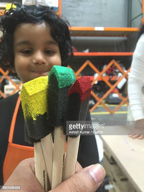 Cropped Hand Holding Paintbrushes Against Cute Boy In Background