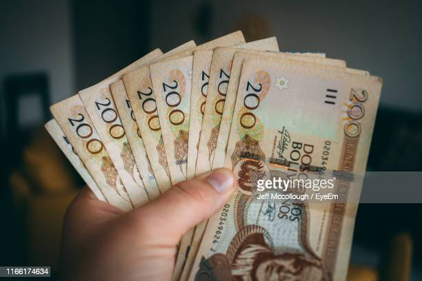 cropped hand holding paper currencies at home - cochabamba stock pictures, royalty-free photos & images