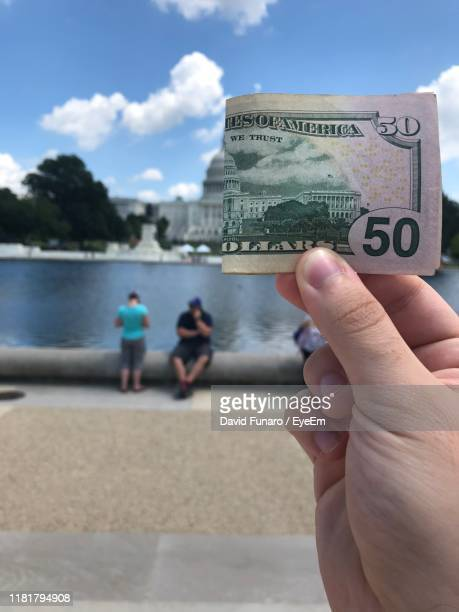 cropped hand holding paper currency against building - washington dc stock pictures, royalty-free photos & images