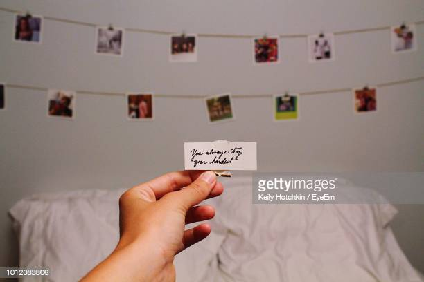 cropped hand holding paper with text against photographs hanging against wall - greeting card stock pictures, royalty-free photos & images