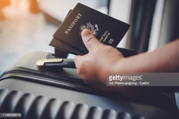 cropped hand holding passport and luggage - passport stock pictures, royalty-free photos & images