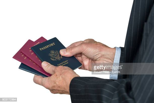 Cropped Hand Holding Passports Against White Background