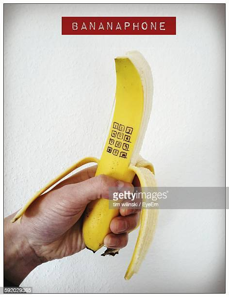 cropped hand holding peeled banana with numbers against white background - 剥いた ストックフォトと画像