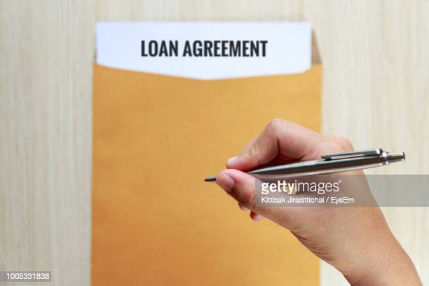Cropped Hand Holding Pen Over Loan Agreement At Table
