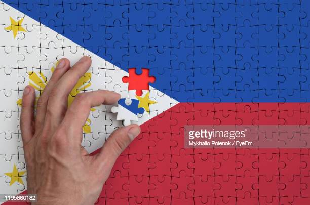 cropped hand holding philippines flag puzzle piece - philippines flag stock pictures, royalty-free photos & images