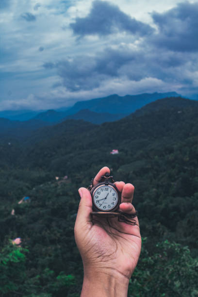 Cropped Hand Holding Pocket Watch Against Mountain