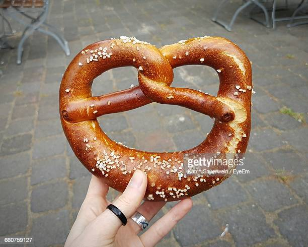 Cropped Hand Holding Pretzel On Footpath