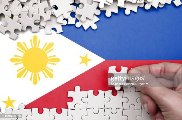 cropped hand holding puzzle piece over philippines flag - philippines flag stock pictures, royalty-free photos & images