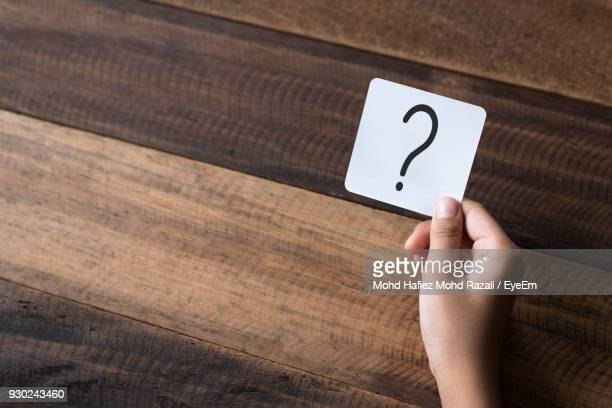 cropped hand holding question mark on paper - questions stock pictures, royalty-free photos & images