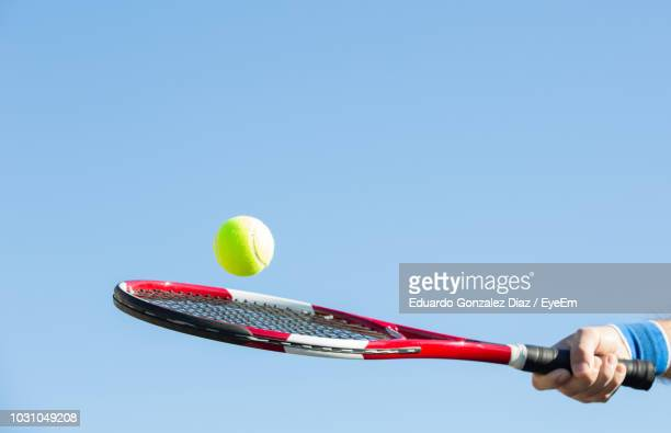 cropped hand holding racket against clear blue sky during sunny day - racquet stock pictures, royalty-free photos & images