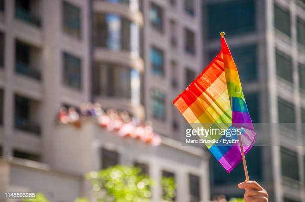 cropped hand holding rainbow flag in city - pride flag stock pictures, royalty-free photos & images