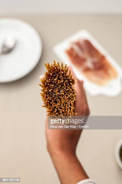 Cropped Hand Holding Raw Spaghetti On Table