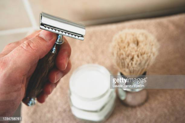 cropped hand holding razor - razor stock pictures, royalty-free photos & images