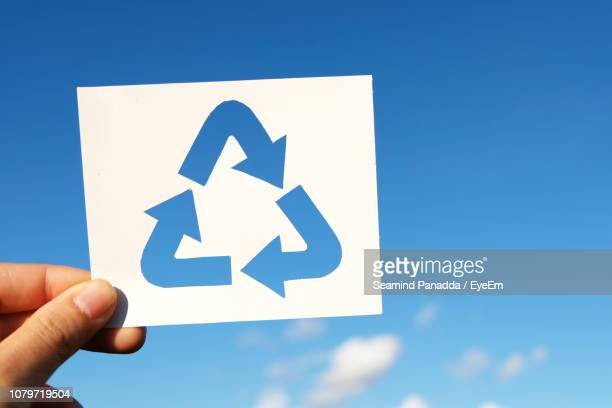 cropped hand holding recycling symbol on paper against sky - recycling stock-fotos und bilder