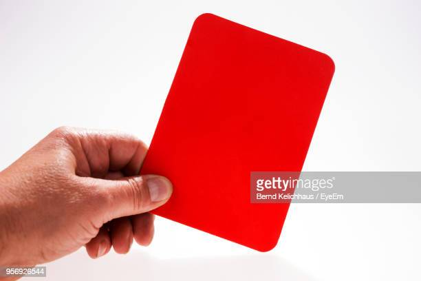 Cropped Hand Holding Red Card Against White Background
