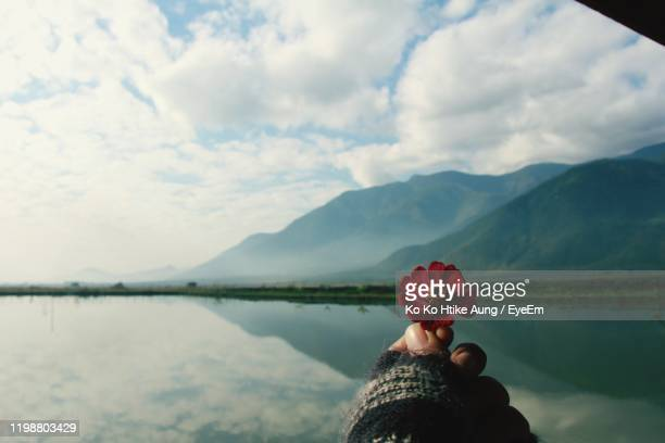 cropped hand holding red flower by lake and mountains against cloudy sky - ko ko htike aung stock pictures, royalty-free photos & images