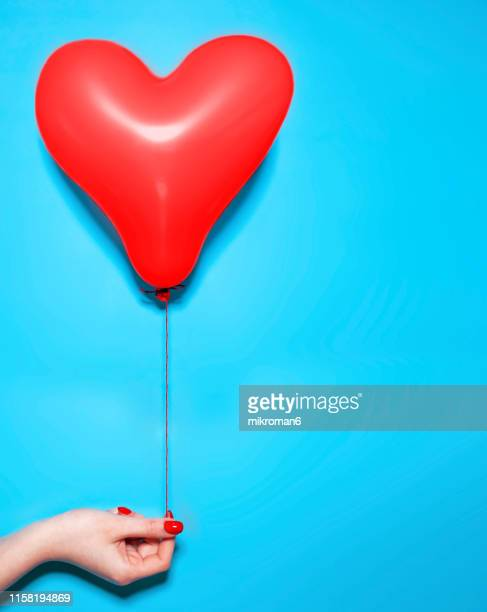 cropped hand holding red heart shape balloon against blue background - valentines day stock pictures, royalty-free photos & images