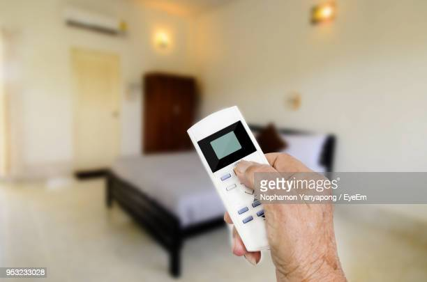 Cropped Hand Holding Remote Control Of Air Conditioner At Home