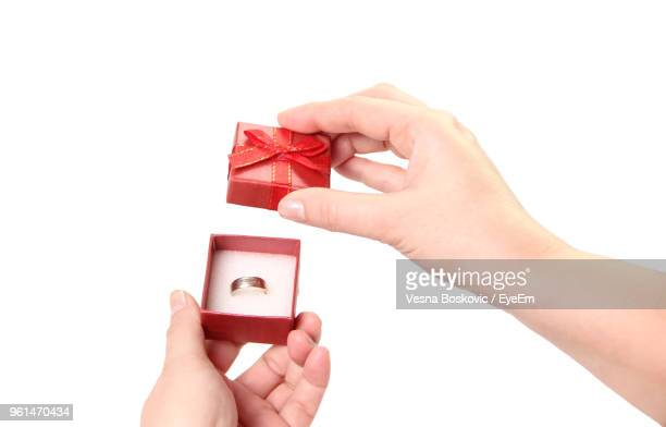 cropped hand holding ring against white background - engagement ring box stock photos and pictures