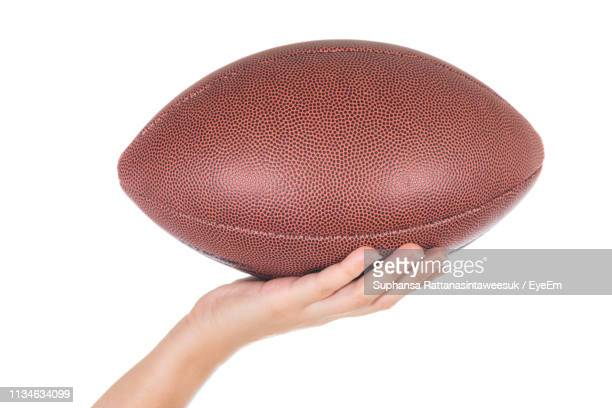 cropped hand holding rugby ball against white background - ラグビーボール ストックフォトと画像