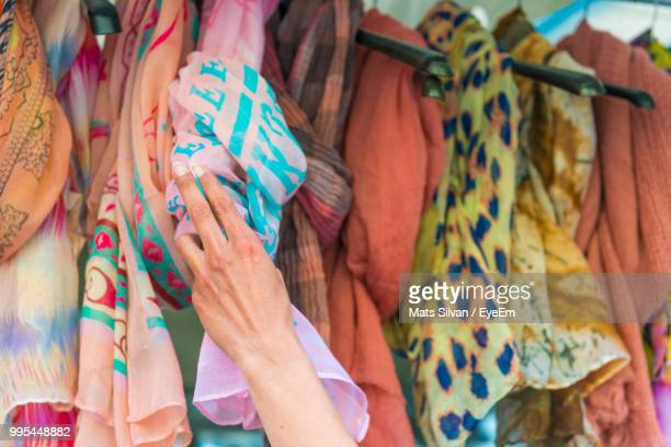 Cropped Hand Holding Scarf Hanging For Sale At Market