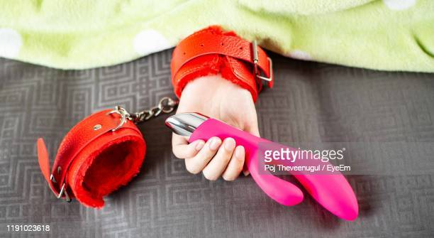 cropped hand holding sex toy with handcuffs - gode photos et images de collection