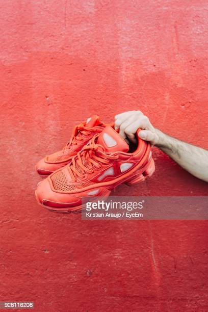 Cropped Hand Holding Shoes Against Red Wall