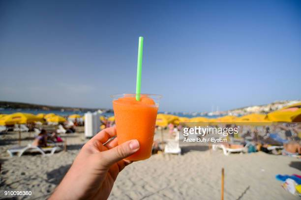 cropped hand holding slush at beach against clear sky - slush stock photos and pictures