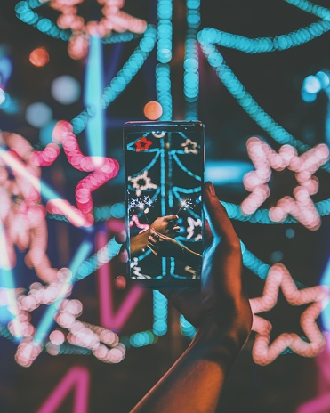 Cropped Hand Holding Smart Phone Against Illuminated Christmas Tree - gettyimageskorea