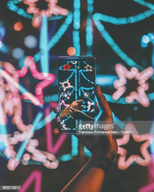 Cropped Hand Holding Smart Phone Against Illuminated Christmas Tree
