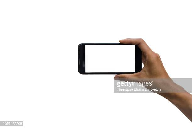 cropped hand holding smart phone against white background - horizontal stock-fotos und bilder