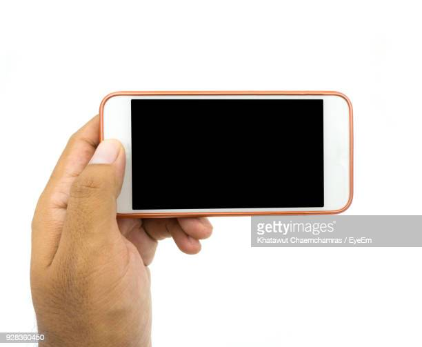 Cropped Hand Holding Smart Phone Against White Background