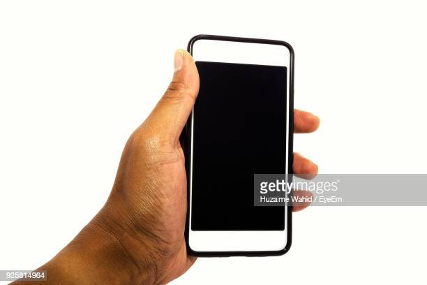 Cropped Hand Holding Smart Phone Over White Background