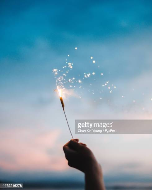 cropped hand holding sparkler against sky during sunset - sparkler stock pictures, royalty-free photos & images