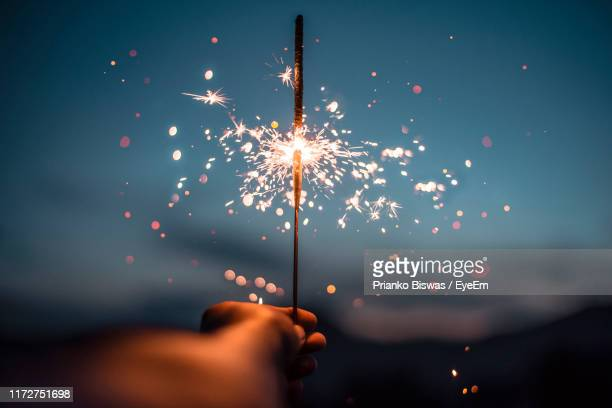 cropped hand holding sparkler at night - sparkler stock pictures, royalty-free photos & images