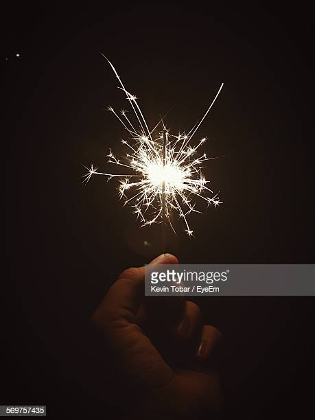 Cropped Hand Holding Sparkler In Dark
