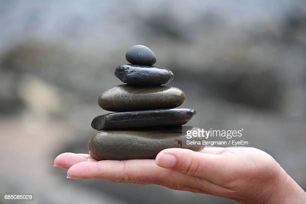 cropped hand holding stacked pebbles - pebble stock photos and pictures
