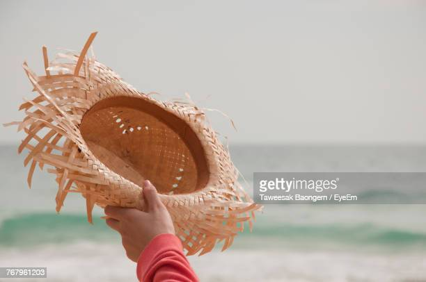 Cropped Hand Holding Straw Hat Against Clear Sky