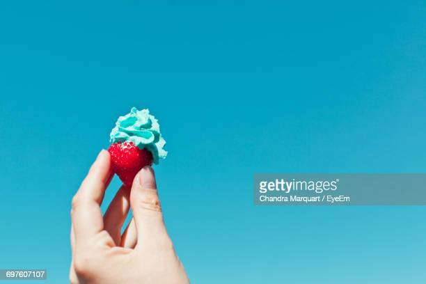 Cropped Hand Holding Strawberry With Whipped Cream Against Clear Blue Sky