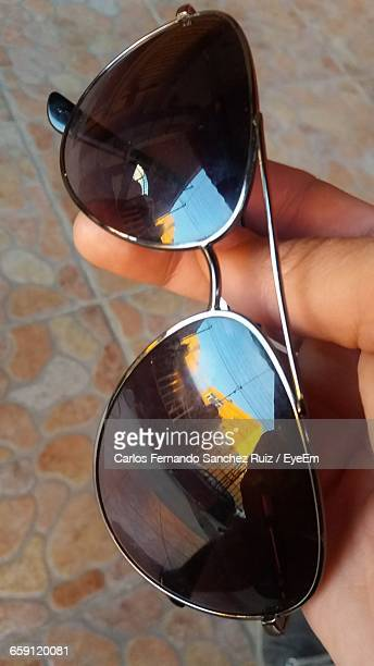 Cropped Hand Holding Sunglass On Footpath