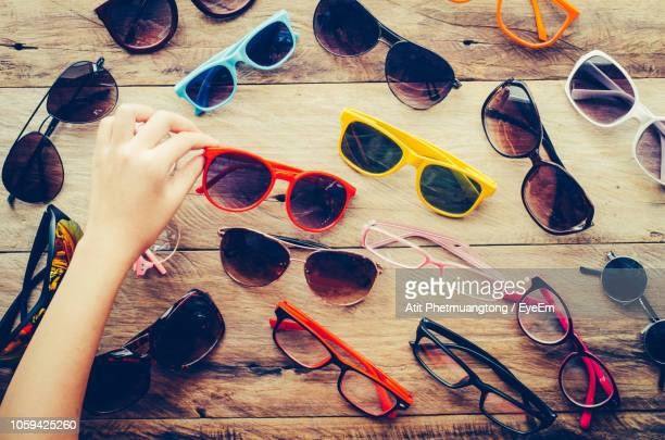 cropped hand holding sunglass on table - eyeem collection stock pictures, royalty-free photos & images