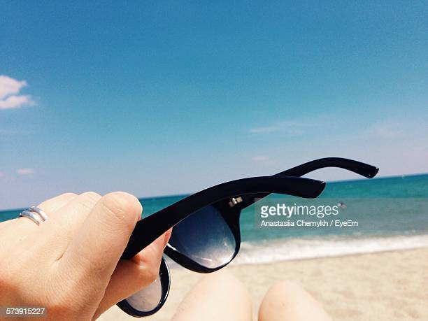 Cropped Hand Holding Sunglasses On Beach Against Blue Sky