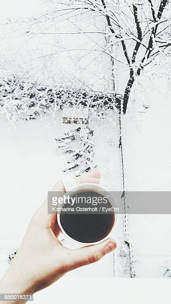cropped hand holding tea cup over bicycle during snowfall - hot drink stock pictures, royalty-free photos & images