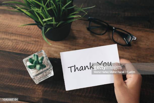 Cropped Hand Holding Thank You Card By Plants Over Table